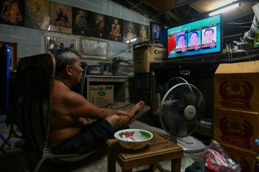 A man watches election results on television in his home in Bangkok on March 24, 2019 after polls closed in Thailand's general election