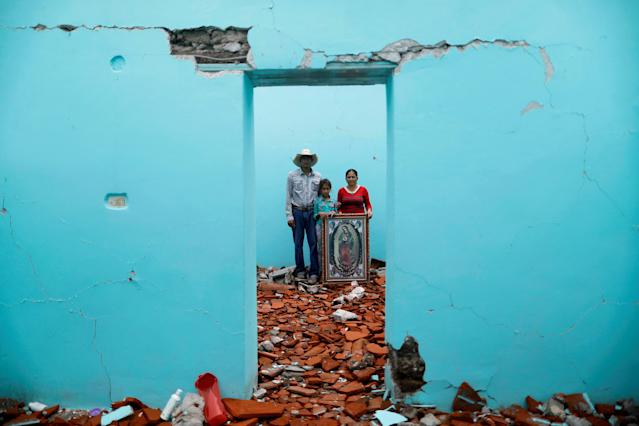"<p>Luis Medina, 36, a farm worker, Maria Teresa Espinoza, 35, housewife, and Maria de Jesus Medina, 9, pose for a portrait inside their house which was badly damaged after an earthquake in San Jose Platanar, at the epicentre zone, Mexico, September 28, 2017. They were able to rescue some furniture and are waiting for their home to be demolished. They are living in their backyard and hope for it to be rebuilt. ""The most valuable thing that I recovered was the picture of the Virgin,"" Espinoza said. (Photo: Edgard Garrido/Reuters) </p>"