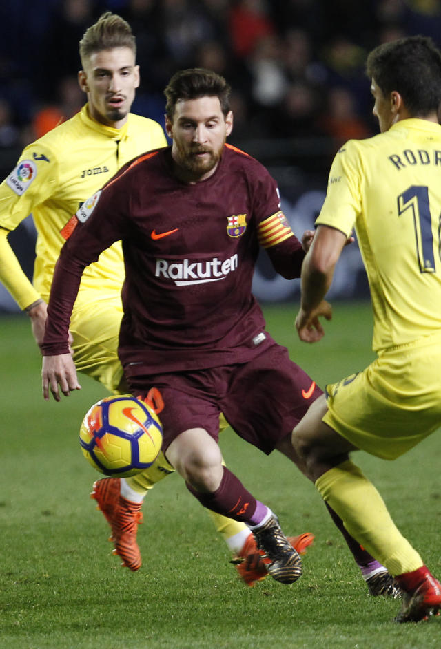 Barcelona's Lionel Messi , center, duels for the ball with Villarreal's Rodrigo, left, during the Spanish La Liga soccer match between Villarreal and FC Barcelona at the Ceramica stadium in Villarreal, Spain, Sunday, Dec. 10, 2017. (AP Photo/Alberto Saiz)