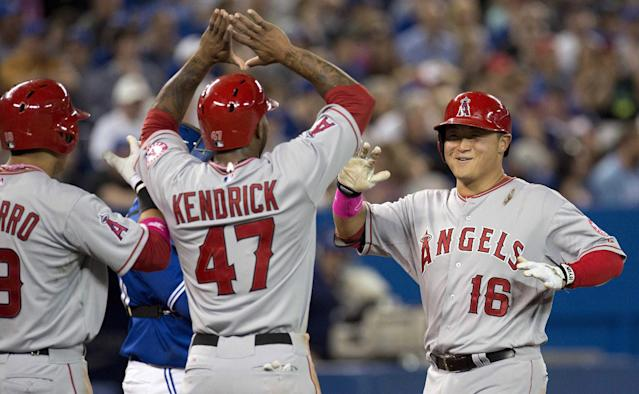 Los Angeles Angels' Hank Conger, right, is congratulated by teammates Efren Navarro, left, and Howie Kendrick after hitting a three-run home run off Toronto Blue Jays pitcher Marcus Stroman during sixth-inning baseball game action in Toronto, Sunday, May 11, 2014. (AP Photo/The Canadian Press, Frank Gunn)
