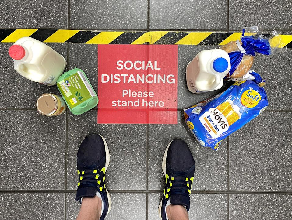 Image: Food shopping next to a social distancing sign at a British supermarket in April. (Paul Child / Reuters file)