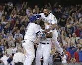 Los Angeles Dodgers' Juan Uribe, left, Yasiel Puig, center, and Matt Kemp, top, celebrate after Uribe scored the winning run after Andre Ethier's grounder and a throwing error by Los Angeles Angels' David Freese during the ninth inning of a baseball game Tuesday, Aug. 5, 2014, in Los Angeles. The Dodgers won 5-4. (AP Photo/Jae C. Hong)