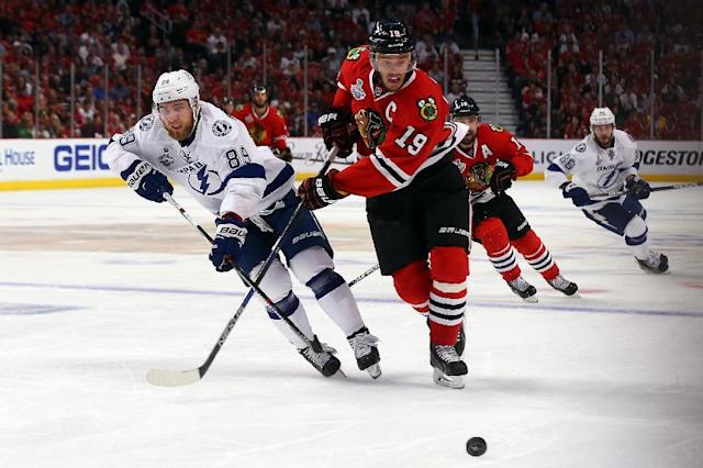 Nikita Nesterov (L) of the Tampa Bay Lightning and Jonathan Toews of the Chicago Blackhawks skate for a loose puck during Game Four of the 2015 NHL Stanley Cup Final at the United Center on June 10, 2015 in Chicago, Illinois (AFP Photo/Bruce Bennett)