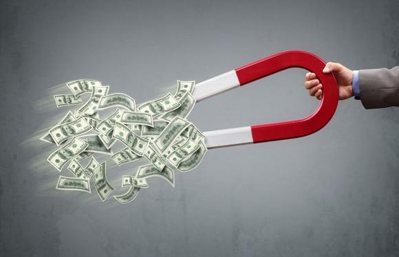 A hand is holding a huge magnet, which has pulled lots of U.S. currency toward it.