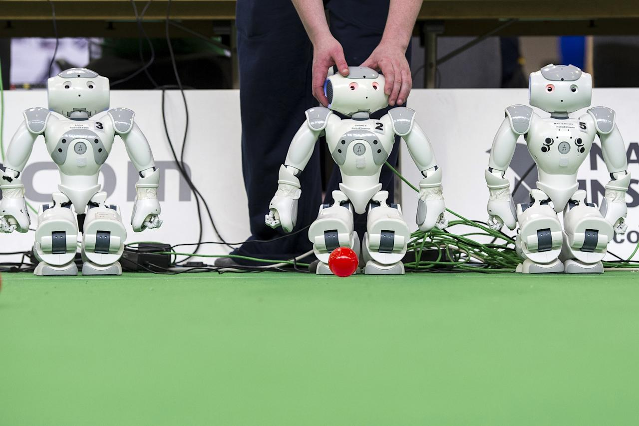 MAGDEBURG, GERMANY - APRIL 26:  A participant checks a robot at the 2013 RoboCup German Open tournament on April 26, 2013 in Magdeburg, Germany. The robots, which are a model called Nao, manufactured by Aldebaran Robotics, perform autonomously and communicate with one another via WLAN. The three-day tournament is hosting 43 international teams and 158 German junior teams that compete in a variety of disciplines, including soccer, rescue and dance.  (Photo by Jens Schlueter/Getty Images)