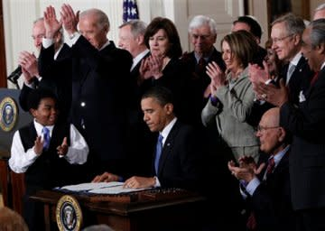 President Obama signs the health care bill into law.