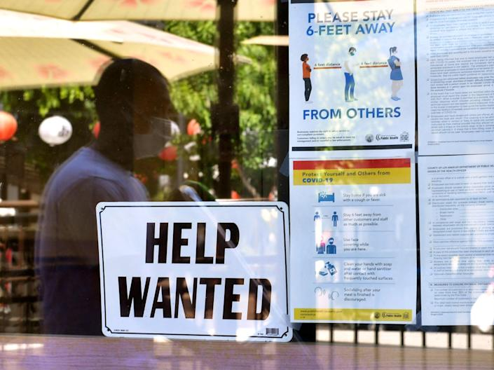A 'Help Wanted' sign is posted beside Coronavirus safety guidelines in front of a restaurant in Los Angeles, California on 28 May 2021 (AFP via Getty Images)