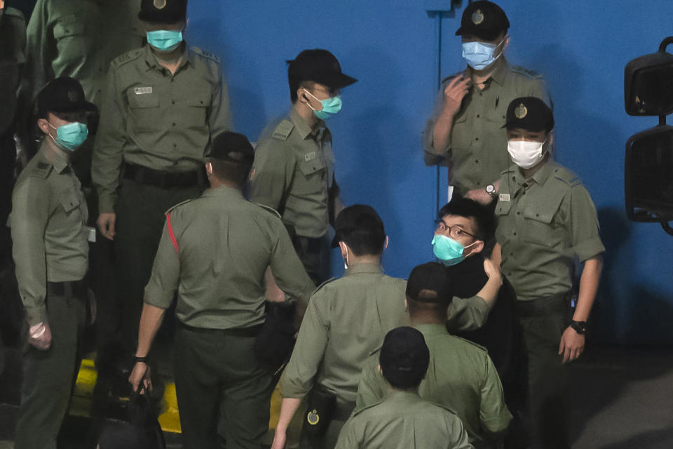 FILE - In this Tuesday, March 2, 2021, file photo, Joshua Wong, right, one of the 47 pro-democracy Hong Kong activists, is escorted by Correctional Services officers to prison in Hong Kong, early Tuesday, March 2, 2021. In the semi-autonomous city of Hong Kong, China is moving to eliminate the possibility of opposition politicians gaining office, saying only patriots loyal to the Communist Party can have a role in government. (AP Photo/Kin Cheung, File)