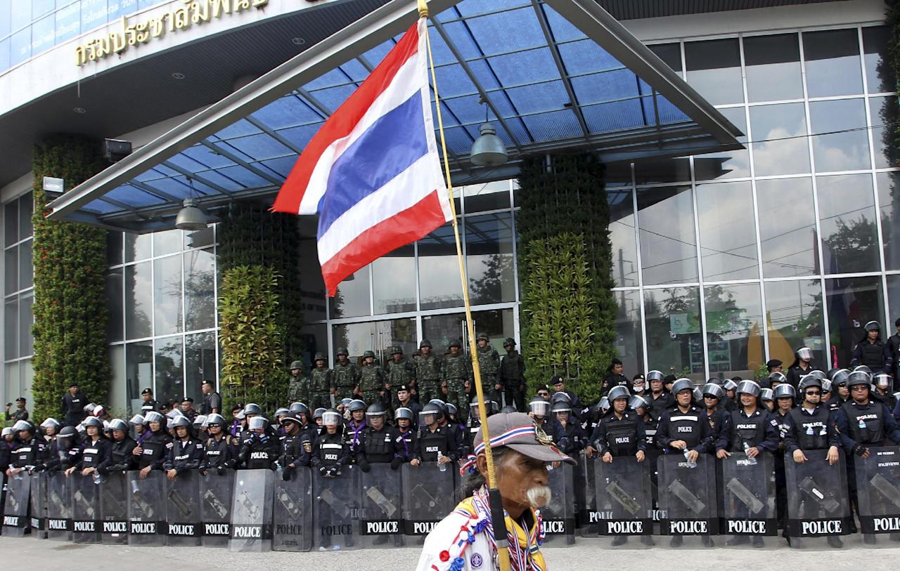 An anti-government protester carries a national flag and walks past line of riot police officers and soldiers guarding the National Broadcasting of Thailand (NBT) building after protesters entering the compound during a rally Friday, May 9, 2014 in Bangkok, Thailand. Thai police fired tear gas and water cannons Friday to push back hundreds of protesters trying to force their way into a government compound, the latest indication that ousting the premier will not solve the country's tense political crisis. (AP Photo/Apichart Weerawong)