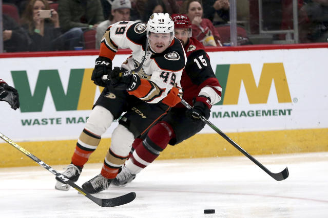 Anaheim Ducks' Max Jones (49) chases the puck against the Arizona Coyotes' Brad Richardson (15) during the first period of an NHL hockey game Wednesday, Nov. 27, 2019, in Glendale, Ariz. (AP Photo/Darryl Webb)