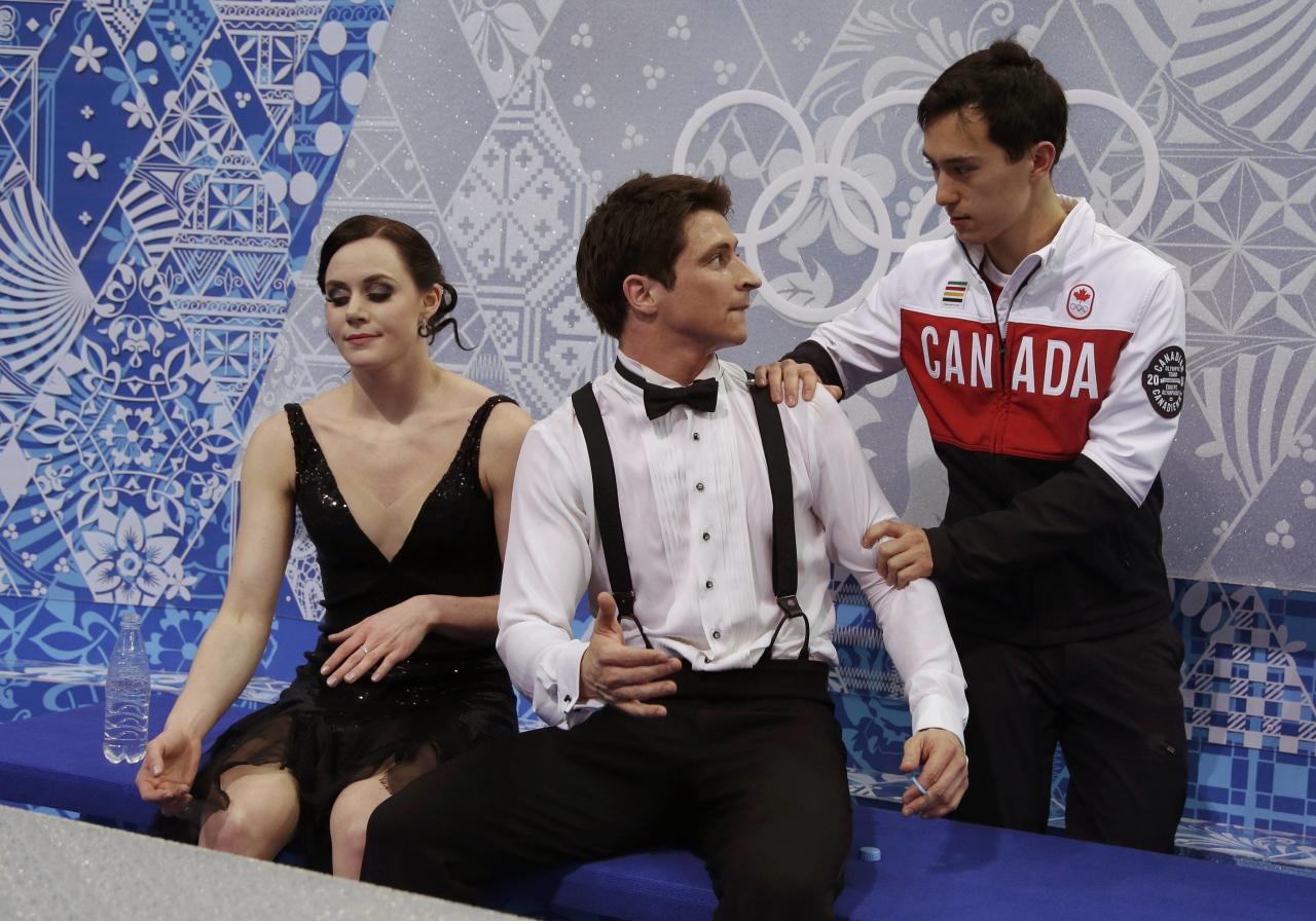 "Tessa Virtue and Scott Moir of Canada react with teammate Patrick Chan (R) in the ""kiss and cry"" area during the Team Ice Dance Short Dance at the Sochi 2014 Winter Olympics, February 8, 2014. REUTERS/Darron Cummings/Pool (RUSSIA - Tags: SPORT FIGURE SKATING SPORT OLYMPICS)"