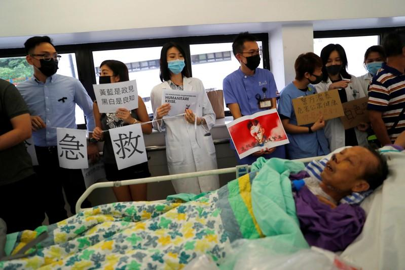 FILE PHOTO: A patient is wheeled past as healthcare staff hold posters and participate in a human chain to protest against what they say is police brutality during the anti-extradition bill protests, at Queen Mary Hospital, in Hong Kong