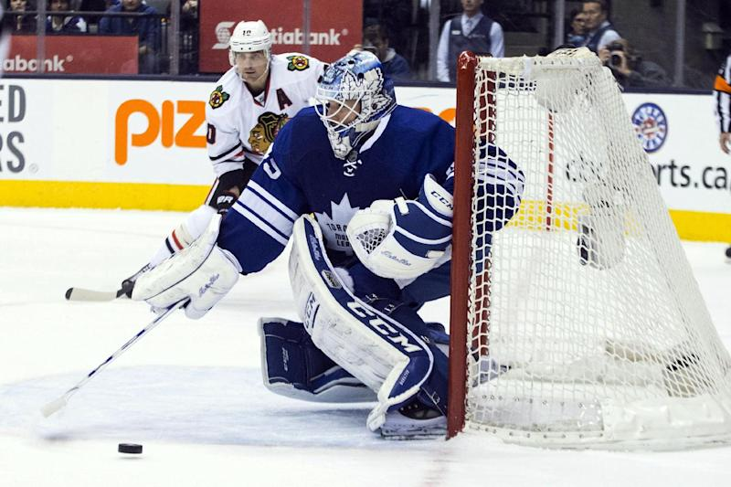 Toronto Maple Leafs goaltender Jonathan Bernier, right, is beaten by a shot from Chicago Blackhawks Patrick Kane as Chicago's Patrick Sharp is near during the first period of an NHL hockey game in Toronto on Saturday, Dec. 14, 2013. (AP Photo/The Canadian Press, Chris Young)