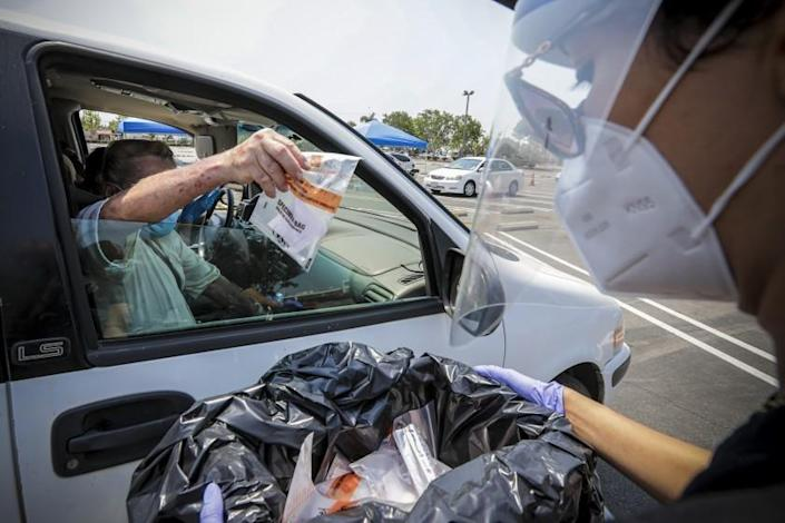 SANTA ANA , CA - AUGUST 22: Daniel Mendoza deposits specimen bag at a drive-in free COVID-19 testing site established by City of Santa Ana and Rancho Santiago Community College district in Santa Ana College parking lot on Saturday, Aug. 22, 2020 in Santa Ana , CA. (Irfan Khan / Los Angeles Times)