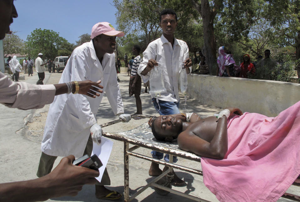 Somalis move a man wounded in a blast at the Somali National Theater in Mogadishu, Somalia Wednesday, April 4, 2012. A suicide blast during a ceremony at Somalia's newly reopened national theater on Wednesday killed at least 10 people, including two of the country's top sports officials, officials said. (AP Photo/Mohamed Sheikh Nor)