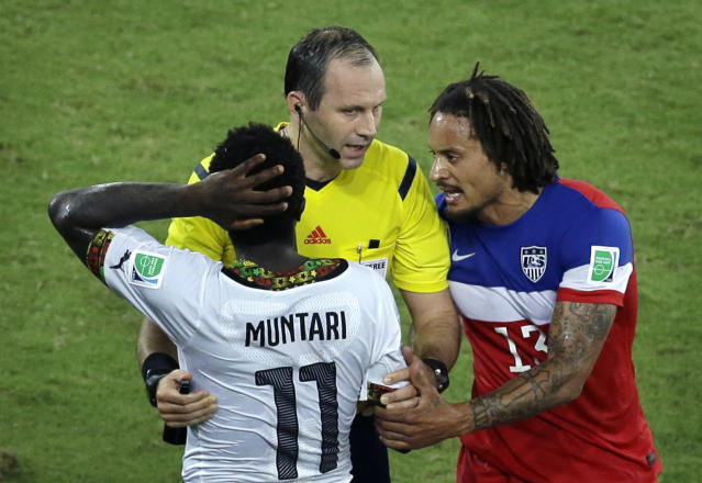 Referee Jonas Eriksson from Sweden, center, mediates an argument between Ghana's Sulley Muntari, left, and United States' Jermaine Jones during the group G World Cup soccer match between Ghana and the United States at the Arena das Dunas in Natal, Brazil, Monday, June 16, 2014. (AP Photo/Hassan Ammar)