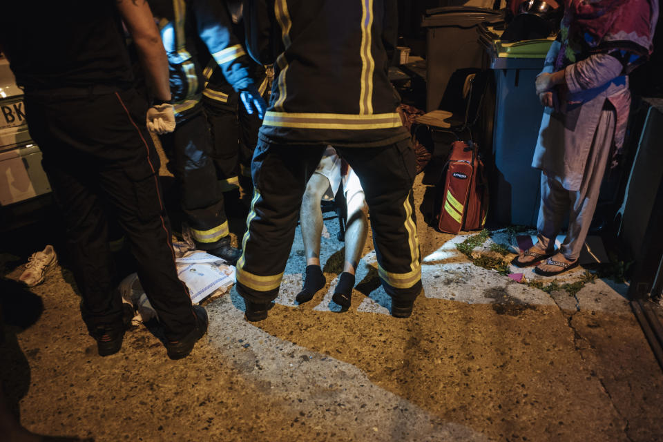 Rescue workers take care of an injured man after a violent brawl, in Paris suburb Villiers-le-Bel, Tuesday, June, 15, 2021. Police who patrol the tough suburbs north of the French capital say they feel that violence is ticking upward. Fights between rival groups are a long-standing problem in the Paris region's depressed neighborhoods, and police say they're increasingly bloody. (AP Photo/Lewis Joly)