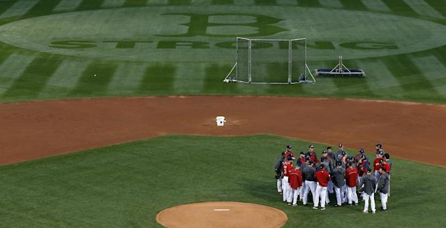 Boston Red Sox players and coaches gather in the infield before a workout at Fenway Park Tuesday, Oct. 22, 2013, in Boston. The Red Sox are scheduled to host the St. Louis Cardinals in Game 1 of baseball's World Series on Wednesday. (AP Photo/Elise Amendola)
