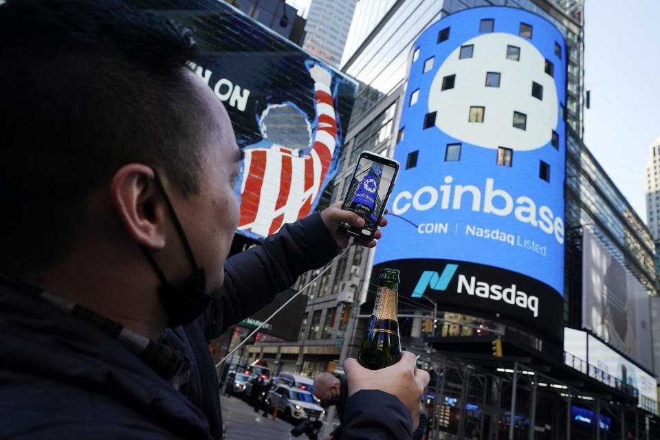 Coinbase employee Daniel Huynh holds a celebratory bottle of champagne as he photographs outside the Nasdaq MarketSite, in New York's Times Square, Wednesday, April 14, 2021. Wall Street will be focused on Coinbase Wednesday with the digital currency exchange becoming a publicly traded company. (AP Photo/Richard Drew)