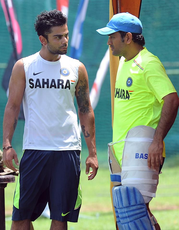 Indian cricketer Virat Kohli (L) speaks with captain Mahendra Singh Dhoni during a training session in Colombo on September 25, 2012.   AFP PHOTO/ LAKRUWAN WANNIARACHCHI