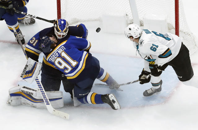 St. Louis Blues' Vladimir Tarasenko (91), of Russia, collides with teammate, goaltender Chad Johnson, as San Jose Sharks' Justin Braun (61) keeps an eye on the puck during the second period of an NHL hockey game Friday, Nov. 9, 2018, in St. Louis. (AP Photo/Jeff Roberson)