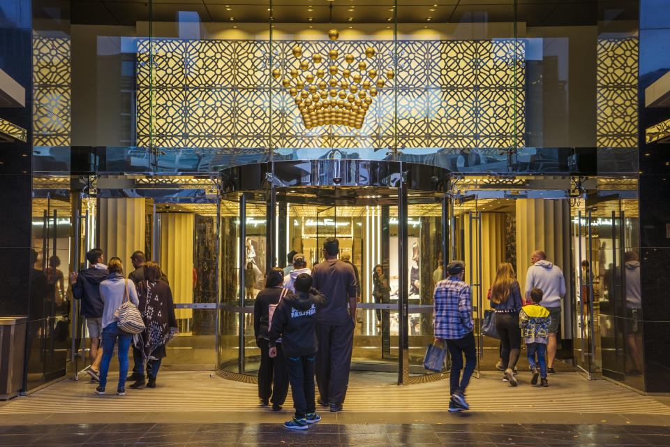 Melbourne, Australia - December 20, 2016: Groups of visitors passing through a entrance to the Crown Melbourne integrated resort in Southbank at dusk.