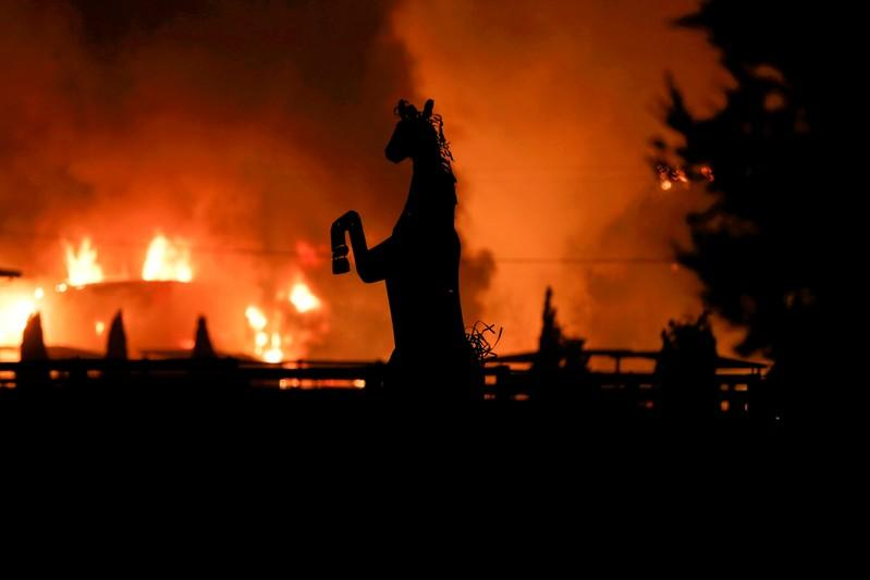 FILE PHOTO: A horse statue is silhouetted by a burning structure during the wind-driven Kincade Fire in Windsor, California