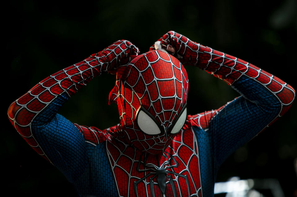 """A member of the """"Desliga da Justica"""" street band gets dressed in his spiderman costume in Rio de Janeiro, Brazil, Sunday, Feb. 14, 2021. The group's performance was broadcast live on social media for those who were unable to participate in the carnival due to COVID restrictions after the city's government officially suspended Carnival and banned street parades or clandestine parties. (AP Photo/Bruna Prado)"""