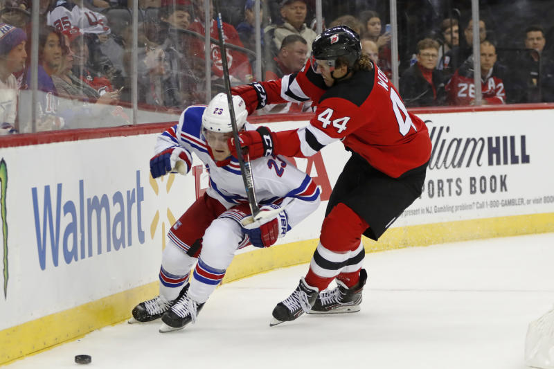 New Jersey Devils left wing Miles Wood (44) defends against New York Rangers defenseman Adam Fox (23) during the second period of an NHL hockey game Thursday, Oct. 17, 2019, in Newark, N.J. (AP Photo/Kathy Willens)