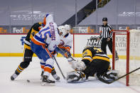 The puck is under New York Islanders' Cal Clutterbuck (15) and Pittsburgh Penguins' Cody Ceci (4) as they battle in front of Penguins goaltender Tristan Jarry (35) during the second period of an NHL hockey game, Saturday, Feb. 20, 2021, in Pittsburgh. (AP Photo/Keith Srakocic)