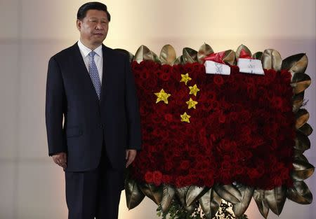 China's President Xi stands next to a flower arrangement depicting China's national flag, in Caracas