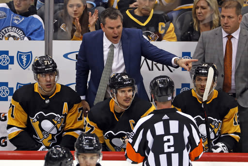 FILE - In this Nov. 18, 2018, file photo, Pittsburgh Penguins head coach Mike Sullivan, top center, gestures while talking to referee Mike Hasenfratz (2) from behind Evgeni Malkin (71), Sidney Crosby (87) and Dominik Simon (12), no longer with the team, during the third period of an NHL hockey game against the Arizona Coyotes in Pittsburgh. Penguins assistant coach Mark Recchi, right rear, no longer with the team, looks on. The faces around Sidney Crosby and Evgeni Malkin change. The expectations around the Pittsburgh Penguins and their two longtime stars do not. After an offseason of retooling the coaching staff and tweaking the roster, the Penguins are hoping to rebound following a second straight early playoff exit. (AP Photo/Gene J. Puskar/File)