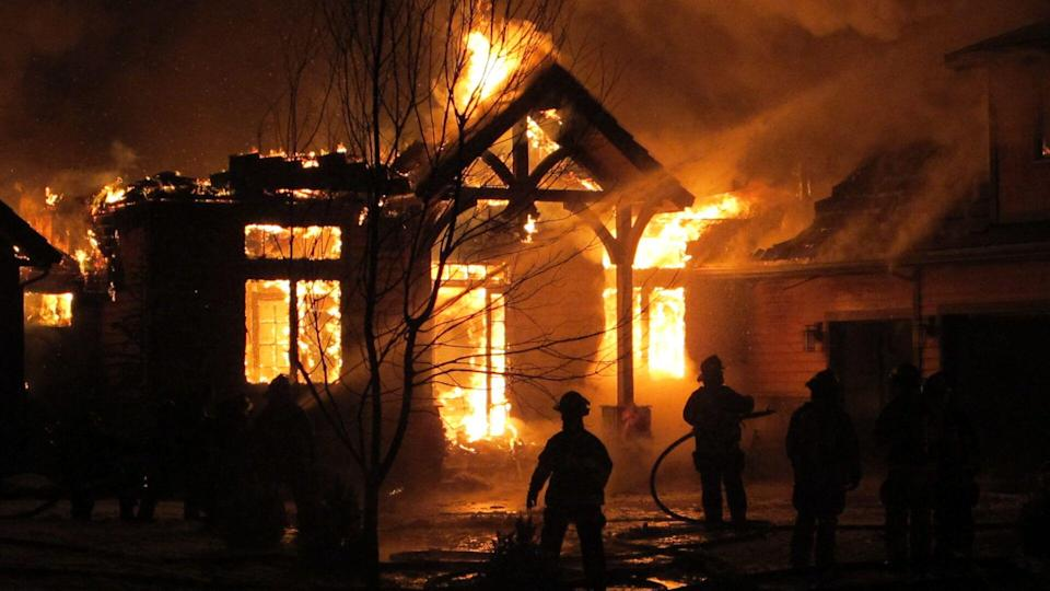 Firemen use a fire hose to try and put out a house fire during a snowfall.