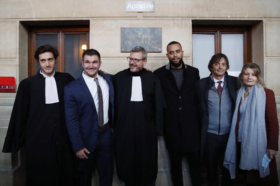 From left, lawyer Louis Cailliez, Alek Skarlatos, lawyer Thibault de Montbrial, Anthony Sadler, Mark Moogalian and Isabelle Risacher Moogalian, pose at the end of their hearing during the Thalys attack trial at the Paris courthouse, Friday, Nov. 20, 2020. Passengers who wrestled and disarmed an Islamic State gunman aboard a high-speed Amsterdam to Paris train are recounting how their split-second decisions helped prevent what could have become a mass slaughter. AP Photo/Francois Mori)