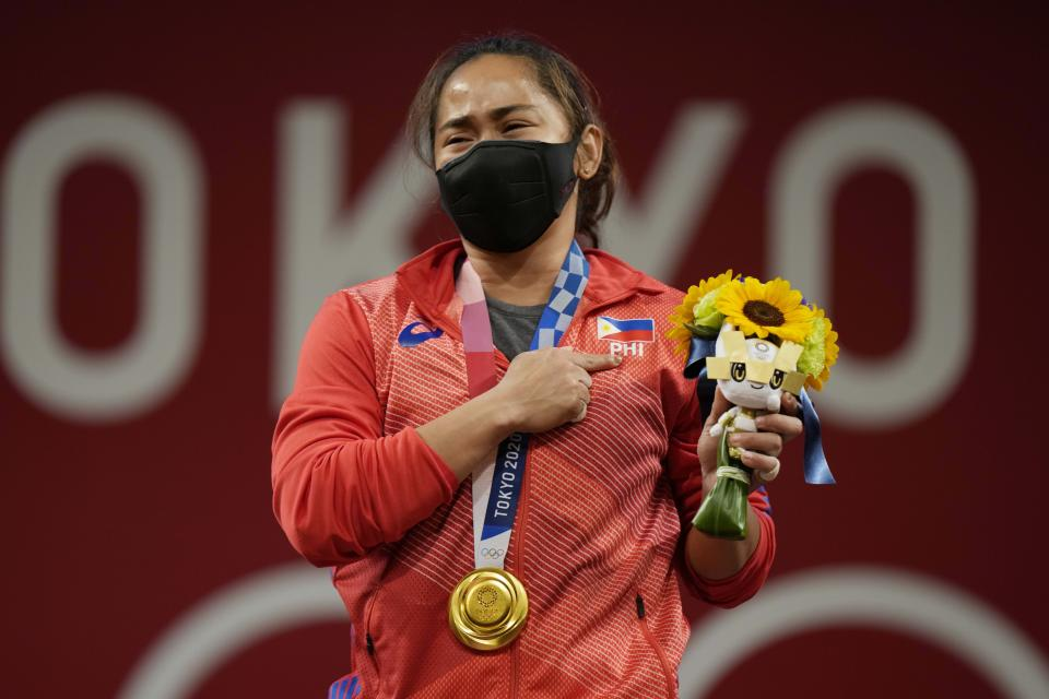 Hidilyn Diaz of Philippines celebrates on the podium after winning the gold medal in the women's 55kg weightlifting event, at the 2020 Summer Olympics, Monday, July 26, 2021, in Tokyo, Japan. (AP Photo/Luca Bruno)
