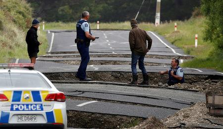 Policemen and locals look at damage following an earthquake, along State Highway One near the town of Ward, south of Blenheim on New Zealand's South Island, November 14, 2016. REUTERS/Anthony Phelps