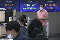 A currency trader passes by screens showing the Korea Composite Stock Price Index (KOSPI), center, and the foreign exchange rate between U.S. dollar and South Korean won, right, at the foreign exchange dealing room of the KEB Hana Bank headquarters in Seoul, South Korea, Friday, April 23, 2021. Asian stock markets were mixed Friday after Wall Street fell following a report that President Joe Biden will propose raising taxes on wealthy investors. (AP Photo/Ahn Young-joon)