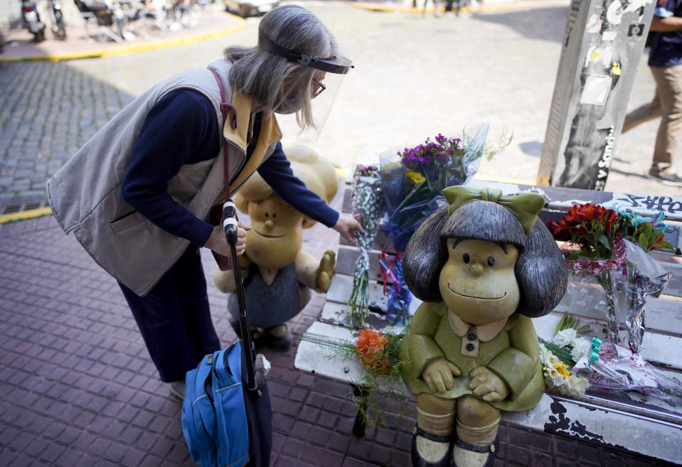 A woman places a flower bouquet next to statue of the comic strip character Mafalda created by Argentine cartoonist Joaquin Salvador Lavado, who was better known as Quino, in Buenos Aires, Argentina, Wednesday, Sept. 30, 2020. Lavado passed away on Wednesday, according to his editor Daniel Divinsky who announced it on social media. He was 88. (AP Photo/Victor R. Caivano)