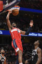 Washington Wizards forward Troy Brown Jr. (6) dunks over Brooklyn Nets guard Caris LeVert (22) and guard Garrett Temple (17) during the first half of an NBA basketball game, Saturday, Feb. 1, 2020, in Washington. (AP Photo/Nick Wass)