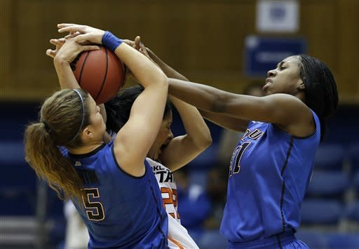 Oklahoma State's Brittney Martin, center, is pressured by DePaul's Anna Martin (5) and Jasmine Penny (31) during the first half of a first-round game in the women's NCAA college basketball tournament in Durham, N.C., Sunday March 24, 2013. (AP Photo/Gerry Broome)