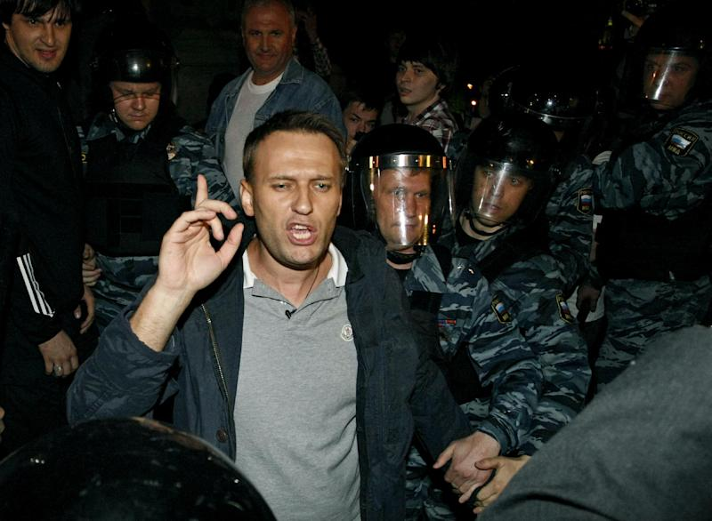 Russian riot police officers detain Alexei Navalny, a prominent anti-corruption whistle blower and blogger, center, while he speaks to protesters gathered near the presidential administrations building in downtown Moscow early Tuesday, May 8, 2012, a day after Putin's inauguration. Vladimir Putin took the oath of office in a brief but regal Kremlin ceremony on Monday, while on the streets outside thousands of helmeted riot police prevented hundreds of demonstrators from protesting his return to the presidency. (AP Photo/Alexander Zemlianichenko Jr )