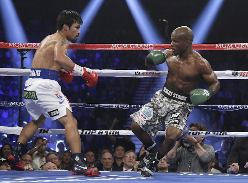 Timothy Bradley, right, loses his footing in front of Manny Pacquiao, of the Philippines, in their WBO welterweight title boxing fight Saturday, April 12, 2014, in Las Vegas. (AP Photo/Isaac Brekken)