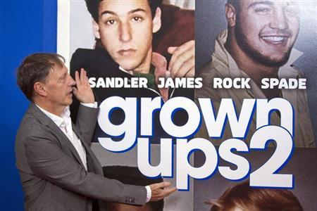 "Director Dennis Dugan gestures to the poster in the backdrop as he arrives for the premiere of the film ""Grown Ups 2"" in New York"