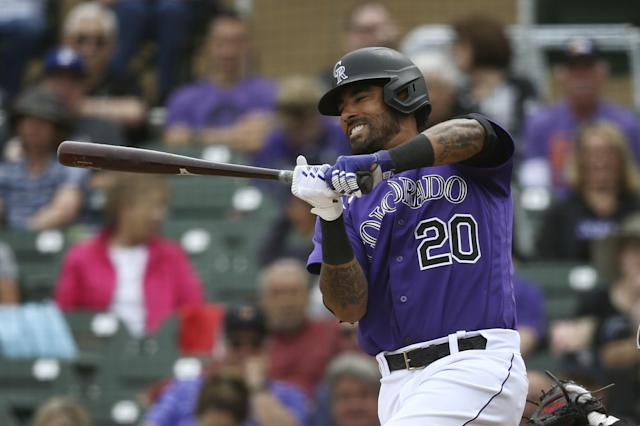 Colorado Rockies' Ian Desmond grimaces on a check swing strike during the fourth inning of a spring training baseball game against the Cincinnati Reds Tuesday, March 10, 2020, in Scottsdale, Ariz. (AP Photo/Ross D. Franklin)