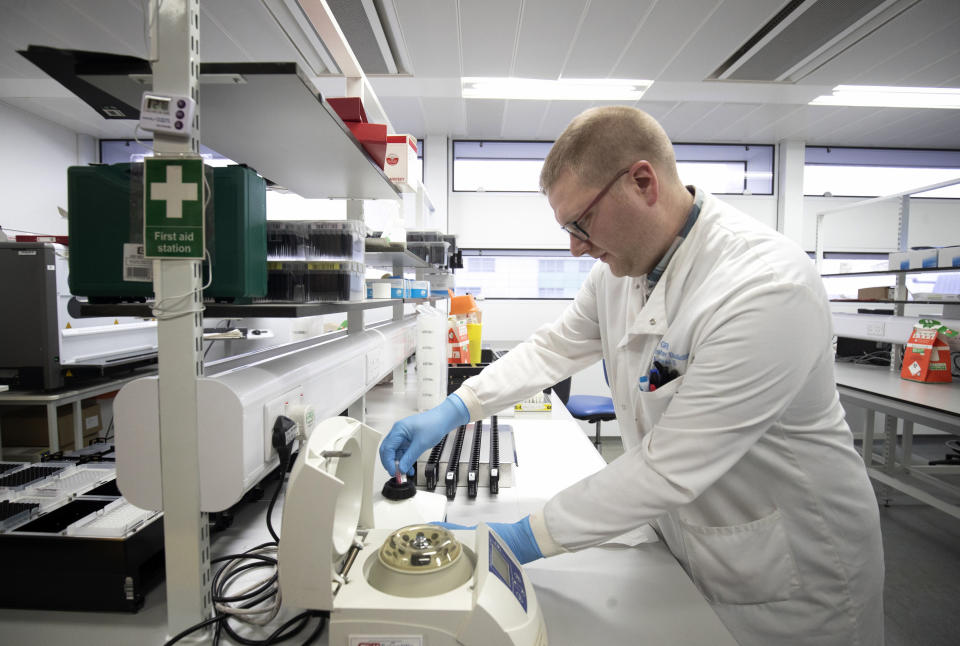 Clinical support technician Douglas Condie extracts viruses from swab samples as analytic work continues to examine the genetic structure of a virus in the coronavirus testing laboratory at Glasgow Royal Infirmary, Glasgow, Scotland, Wednesday Feb. 19, 2020.  The COVID-19 virus originally centred in China now has multiple cases confirmed worldwide. (Jane Barlow/PA via AP)