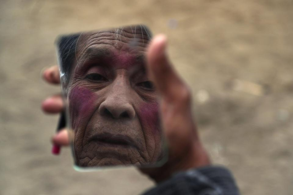 """Circus clown Santos Chiroque, whose performance name is """"Piojito,"""" or Little Tick, looks into a mirror as he demonstrates how he puts on his clown makeup, using just lipstick, outside his home on the outskirts of Lima, Peru, Monday, Aug. 10, 2020. Chiroque's family used to run their own small circus, but since March when the lockdown to curb COVID-19 closed down their business, and the requirement for people over 60 to self-quarantine kept the 74-year-old at home, they started selling circus food like caramelized apples to survive. (AP Photo/Martin Mejia)"""