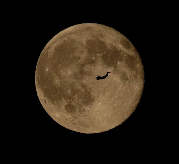 """An airplane flies in front of the """"blue moon"""" full moon of July 31, 2015 in this photo captured by skywatcher Chris Jankowski of Erie, Pennsylvania."""