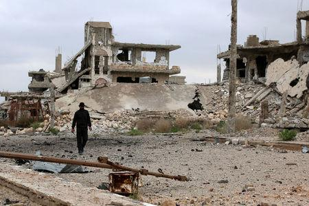 A man walks past damaged buildings in rebel-held area of southern city of Deraa, Syria April 23, 2017. REUTERS/Alaa Al-Faqir