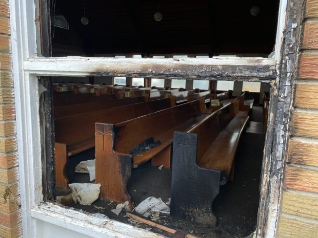 The shattered remains of the window from where the fire apparently started at St. Patrick Co-Cathedral in Yellowknife. The fire, the latest in a string of fires at churches throughout Canada, is being treated as suspicious.  (John Van Dusen/CBC - image credit)