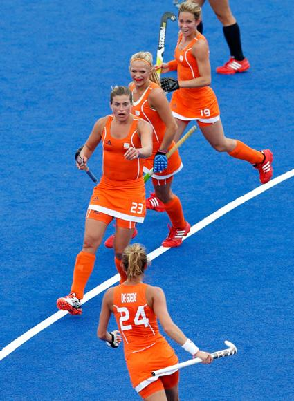 Netherlands' Kim Lammers (23) celebrates with her team mates Eva de Goede (bottom), Kitty van Male and Ellen Hoog (R) after scoring a goal against Belgium during their women's Group A hockey match at the London 2012 Olympic Games at the Riverbank Arena on the Olympic Park in London July 29, 2012. REUTERS/Suzanne Plunkett